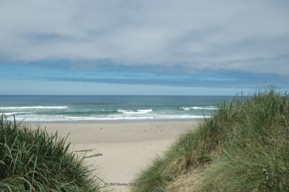 Standing on sand dune looking at ocean waves
