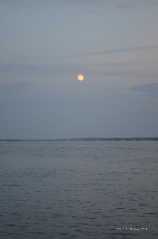 Moon rising over still lake.