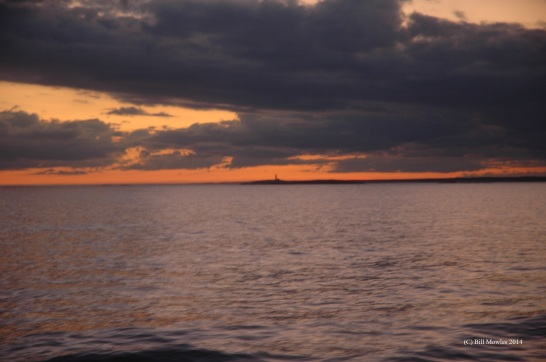 Ocean sunset from ship with distant lighthouse