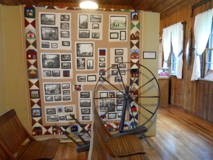 Quilt and spinning wheel on display at Homestead Museum, Crossville, Tennessee.