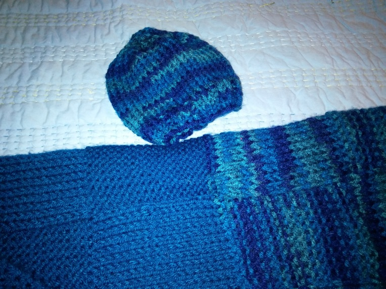 Knitting - baby cap next to blanket