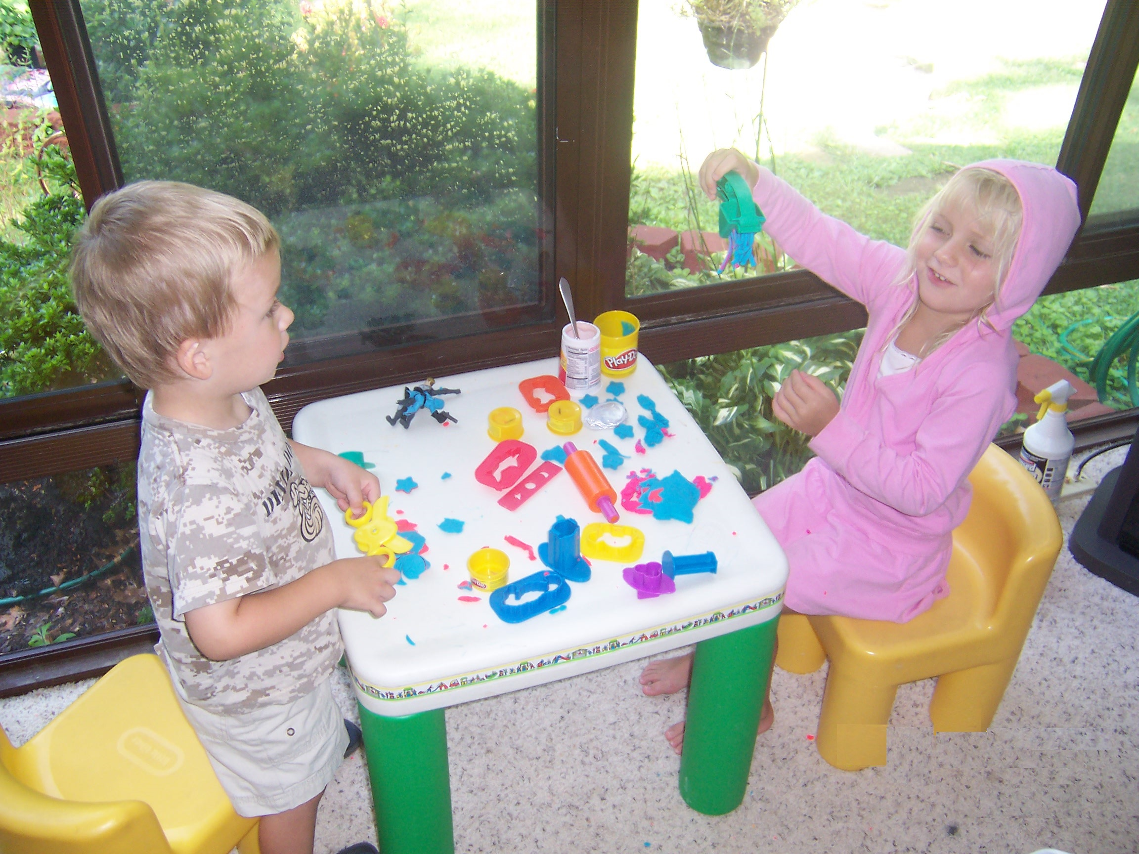 Grandchildren at table playing (C)